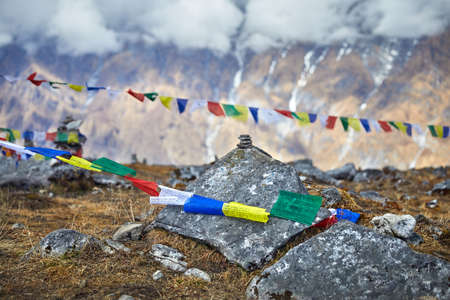 Small piles from stones and Tibetan prayer flags Lung Ta at the Mardi Himal Base Camp at cloudy peaks of Himalaya Mountains in Nepal