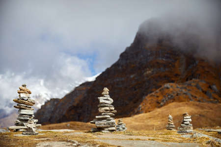 Small piles from stones on the Mardi Himal trek and cloudy peaks of Himalaya Mountains in Nepal Stock Photo