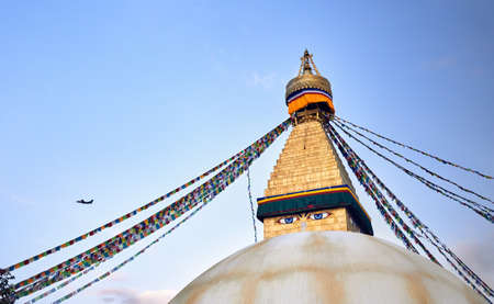 Bodnath Buddhist Stupa with prayer flags and airplane in Kathmandu