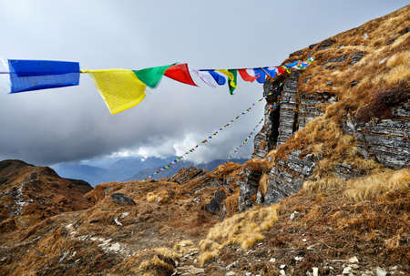 Rocks and Tibetan prayer flags Lung Ta at the Mardi Himal Base Camp at cloudy peaks of Himalaya Mountains in Nepal Stock Photo