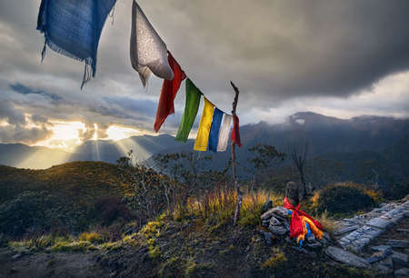 Small piles from stones and Tibetan prayer flags Lung Ta at the Mardi Himal Base Camp at cloudy sunset peaks of Himalaya Mountains in Nepal