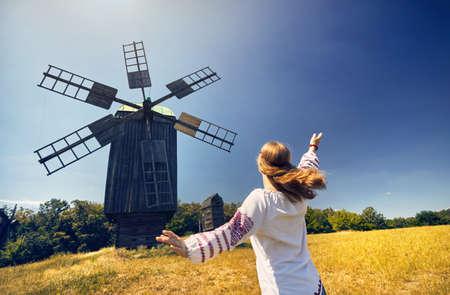 Beautiful Ukrainian girl dancing near wooden wind mill in white ethnic shirt at national architecture museum in Pirogovo. Kiev, Ukraine