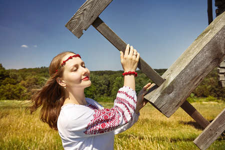Portrait of beautiful Ukrainian girl holding blade of wooden wind mill in white ethnic shirt at architecture museum in Pirogovo. Kiev, Ukraine