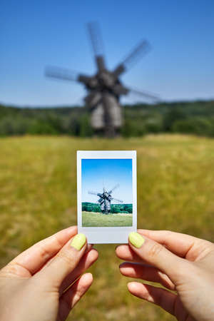 Woman holding photograph of wooden windmill at the meadow in architecture museum in Pirogovo. Kiev, Ukraine