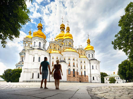 Young tourist couple in silhouette looking at Church with golden domes at Kiev Pechersk Lavra Christian complex. Old historical architecture in Kiev, Ukraine Фото со стока