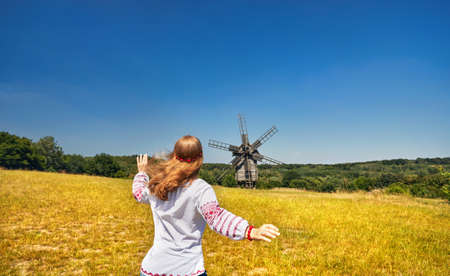 Beautiful Ukrainian girl running to wooden wind mill in white ethnic shirt at national architecture museum in Pirogovo. Kiev, Ukraine