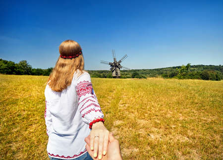 Beautiful Ukrainian girl in white ethnic shirt leading man by hand to wooden wind mill at architecture museum in Pirogovo. Kiev, Ukraine
