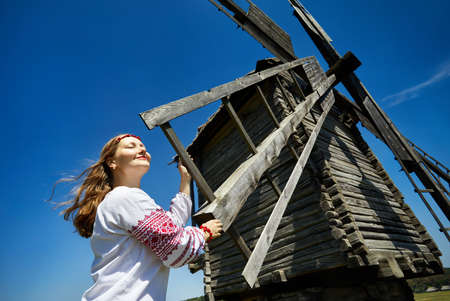 Beautiful Ukrainian girl near wooden wind mill in white ethnic shirt at national architecture museum in Pirogovo. Kiev, Ukraine