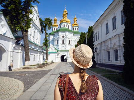 Woman in hat looking at Church with golden domes at Kiev Pechersk Lavra Christian complex. Old historical architecture in Kiev, Ukraine