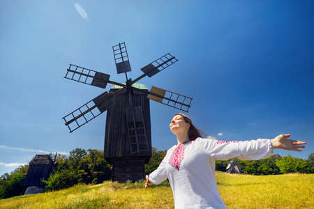 Beautiful Ukrainian girl dancing near wooden wind mill in white ethnic shirt at national architecture museum in Pirogovo. Kiev, Ukraine