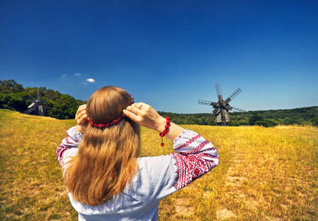 Beautiful Ukrainian girl wearing flower wreath at wooden wind mills background in white ethnic shirt at national architecture museum in Pirogovo. Kiev, Ukraine