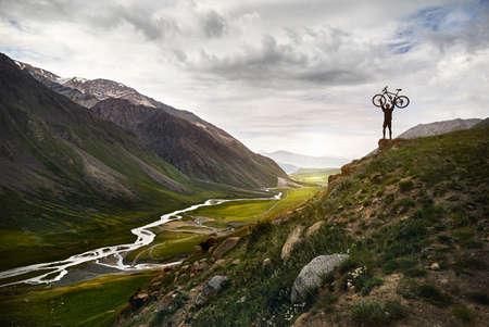 Epische Aufnahme des Mannes, der sein Mountainbike auf dem Hügel in der Silhouette mit dem Fluss im Gebirgstalhintergrund hält.