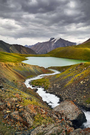 Beautiful Mountain Lake Teshik Kol against cloudy sky in the Terskey Alatay, Kyrgyzstan