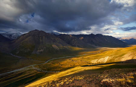 Beautiful landscape of mountain valley at sunrise cloudy sky of Terskey Alatau in Kyrgyzstan