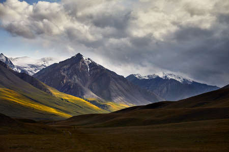 Beautiful landscape of snowy mountain in green valley of Terskey Alatau in Kyrgyzstan 写真素材
