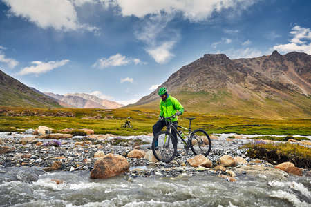 Mann mit Mountainbike, der den Fluss in den wilden Bergen gegen bewölkten Himmelhintergrund kreuzt.