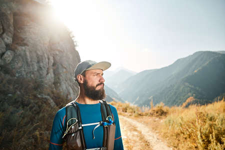 Portrait of bearded runner athlete with backpack in the mountains at sunrise