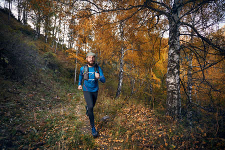 Runner athlete with beard running on the trail in the autumn yellow birch wood