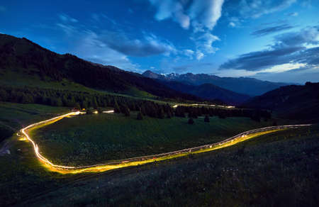 Light trace of runners led on the race in the mountains at twilight sky in Kazakhstan, Central Asia