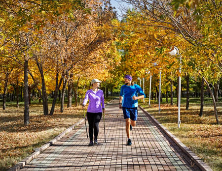 Young couple training in autumn park. Man is jogging and woman doing Nordic walking with poles. Healthy life concept.