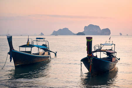 Traditional long tail on the tropical beach at sunset at islands background in Andaman Sea, Thailand