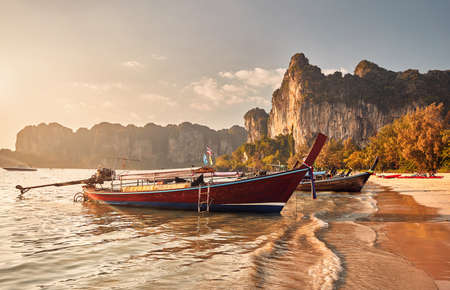 Long tail boats on tropical beach at beautiful sunset in Krabi, Thailand Фото со стока