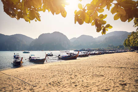 Long tail boats on tropical beach at beautiful sunset on Koh Phi Phi island, Thailand