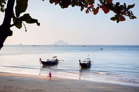 Beautiful woman in pink dress on the tropical beach of Ao Nang province with longtail boat at morning in Thailand.