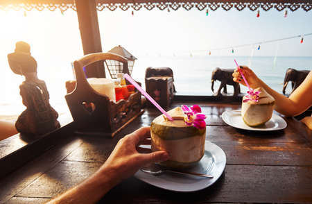 Couple drinks sweet fresh coconuts decorated with flower at restaurant on the beach at sunrise