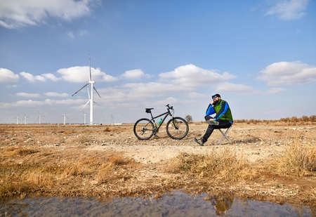 Bearded man resting on the chair with his mountain bicycle near wind farm in the desert