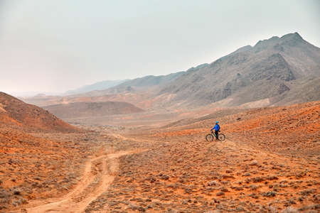Man on mountain bike in blue shirt in the red desert Stock fotó