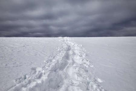 Footprints on the snow against dark overcast sky background