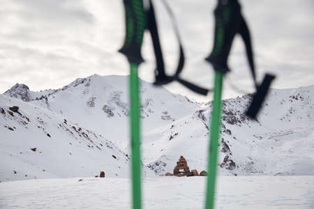 High snowy mountains and trekking poles at foreground. Tourism and trekking concept