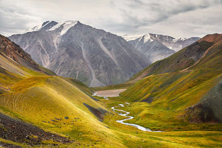 River in the mountain valley at cloudy sky in Kyrgyzstan