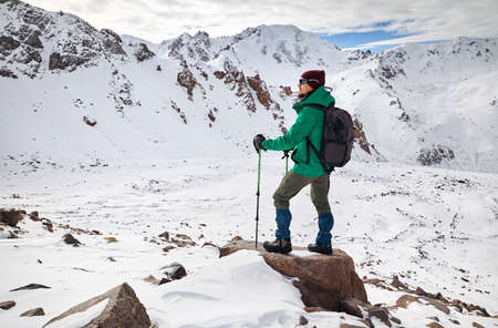 Hiker with trekking poles and backpack standing on the rock at snowy mountains background