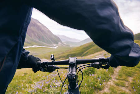 Hands on handlebar of mountain bike at in the mountain road close up