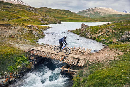Man on mountain bike crossing the river by wooden bridge in the mountain valley 免版税图像