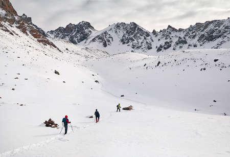 Drei Touristen auf dem Schneeweg erklimmen die Berge Standard-Bild