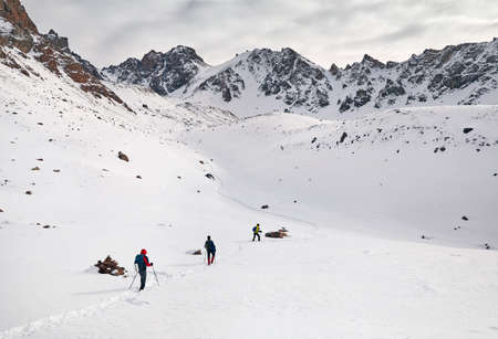 Three tourists on the snow trail climb the mountains Imagens
