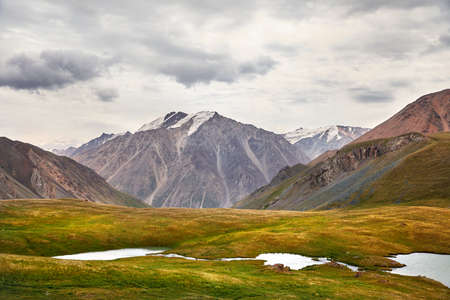 Beautiful Lake and high mountains in the valley against cloudy sky in Kyrgyzstan Stock fotó
