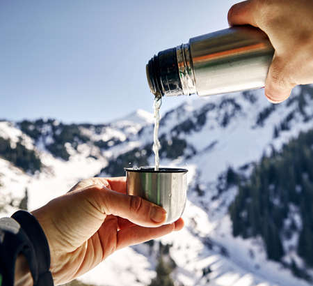 Traveler pouring tea to cup against winter mountain background.