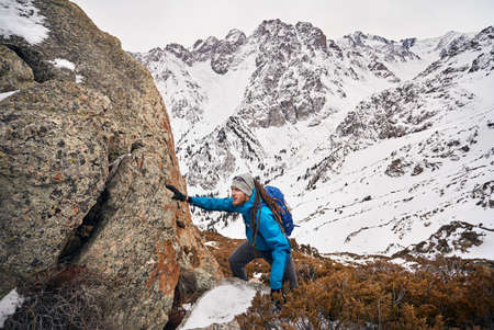 Tourist with dreadlocks climbs the rock at snowy mountains background