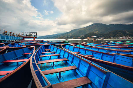 Blue boats at Phewa lake shore in Pokhara, Nepal.