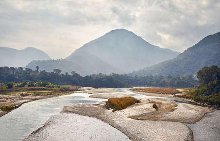 Foggy Mountains and river at Himalayas near Pokhara in Nepal Stock Photo