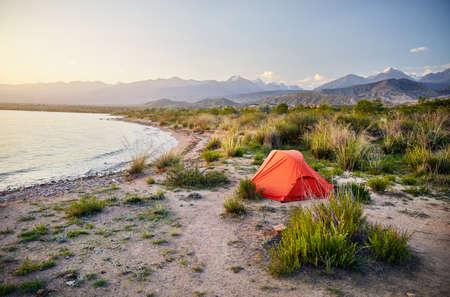 Orange tent on the shore of Issyk Kul mountain lake in Kyrgyzstan