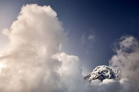 Annapurna South peak surrounded by clouds at sunset in the Himalayas, Nepal.