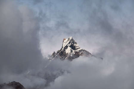 Machapuchare Fish Tale peak surrounded by clouds in the Himalayas, Nepal.