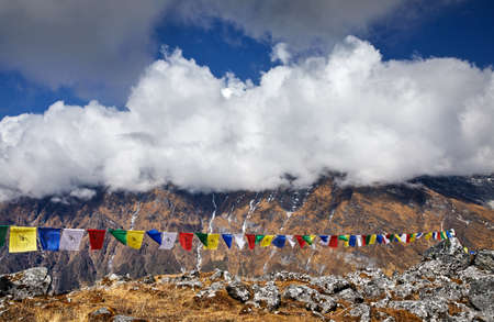 Tibetan prayer flags Lung Ta at the Mardi Himal Base Camp at cloudy peaks of Himalaya Mountains in Nepal