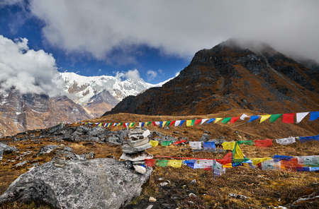 Tibetan prayer flags Lung Ta at the Mardi Himal Base Camp at cloudy peaks of Himalaya Mountains in Nepal
