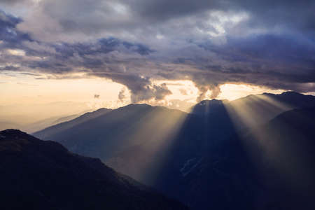 Beautiful Sunet with dramatic clouds and sun rays above the hills in Himalayas in Nepal